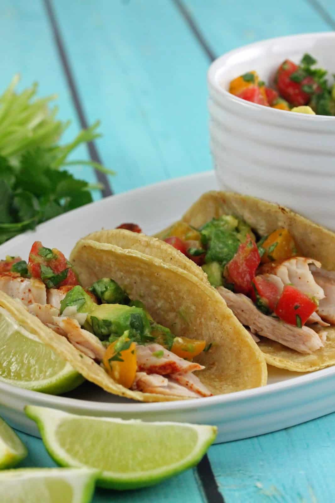 Fish tacos on a plate topped with an avocado tomato salsa and lime wedges