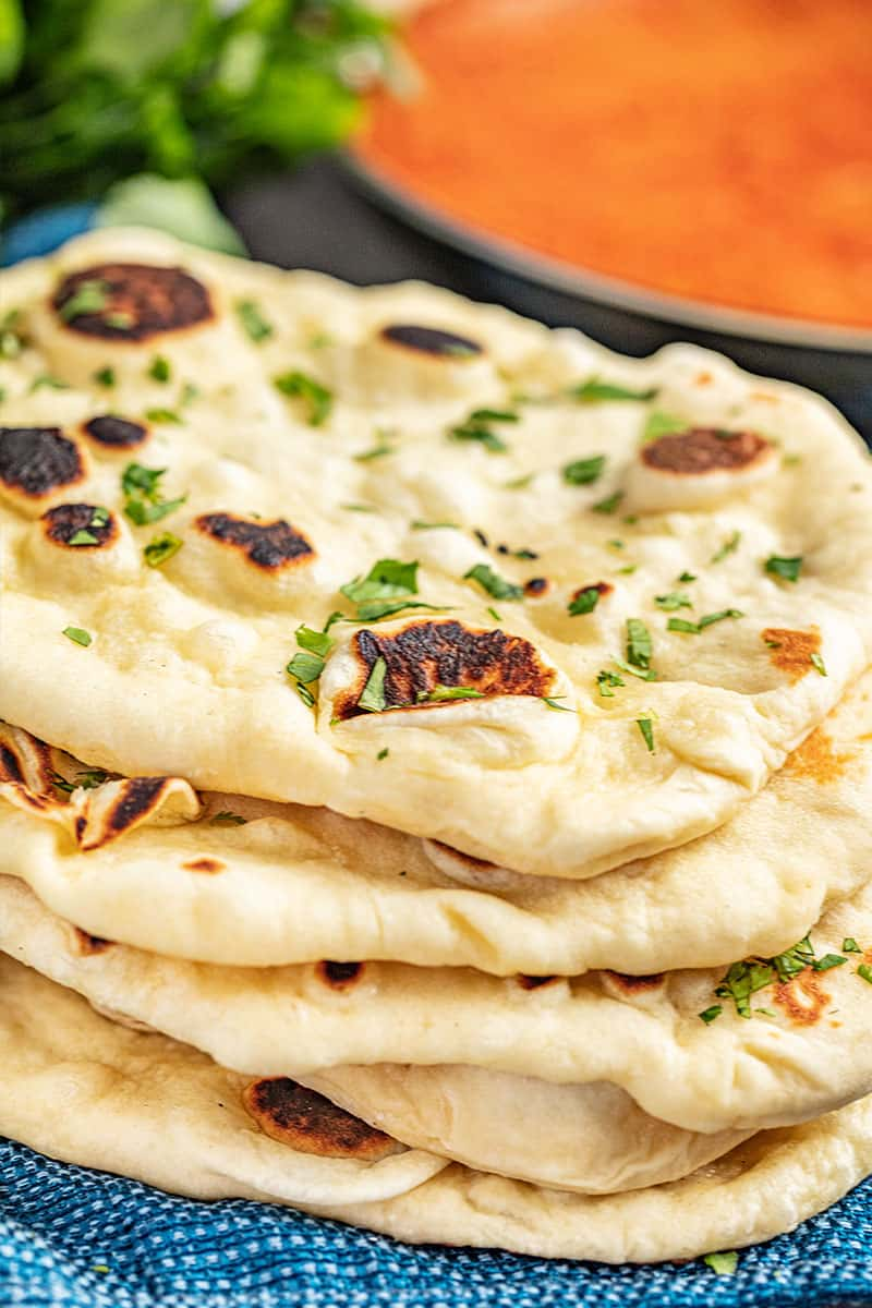 5 pieces of naan bread stacked on top of each other with a pan of tikka masala in the background