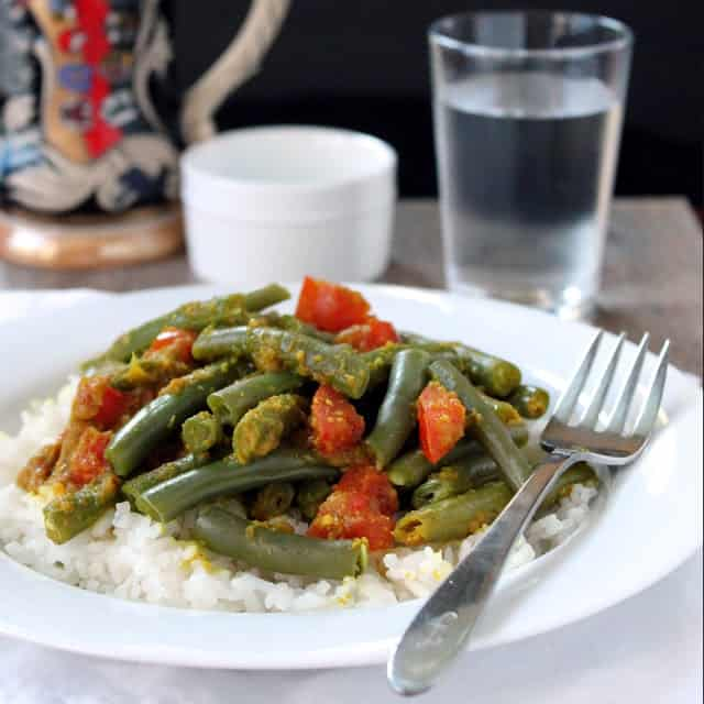Green beans with chunks of tomato served over rice on a white plate with a fork