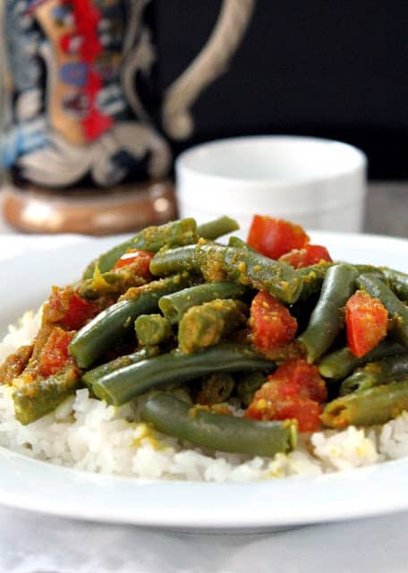 Green beans with chunks of tomato served over rice on a white plate