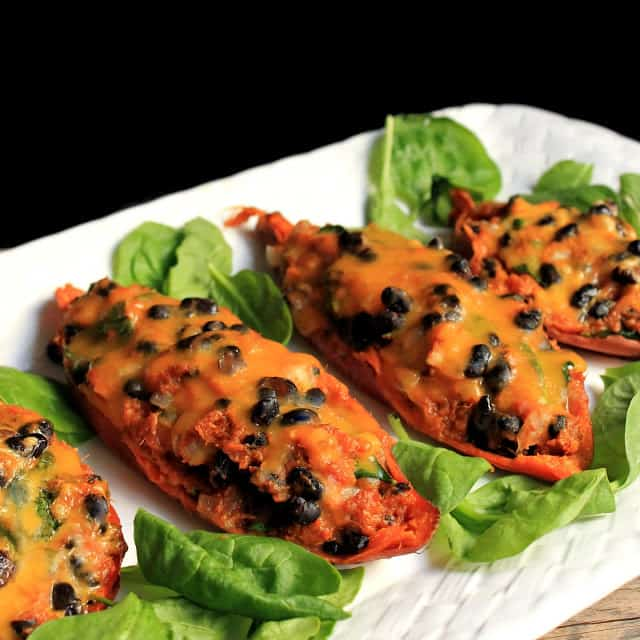 Four Mexican Stuffed Sweet Potatoes on a white plate and garnished with spinach leaves