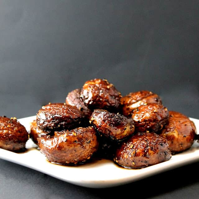 Pile of roasted mushrooms on a white plate