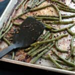 Black spatula resting on a sheet pan with roasted green beans garnished with spicy red pepper flakes
