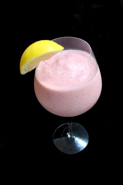 Strawberry Lemonade Smoothie in a wine glass garnished with a lemon wedge