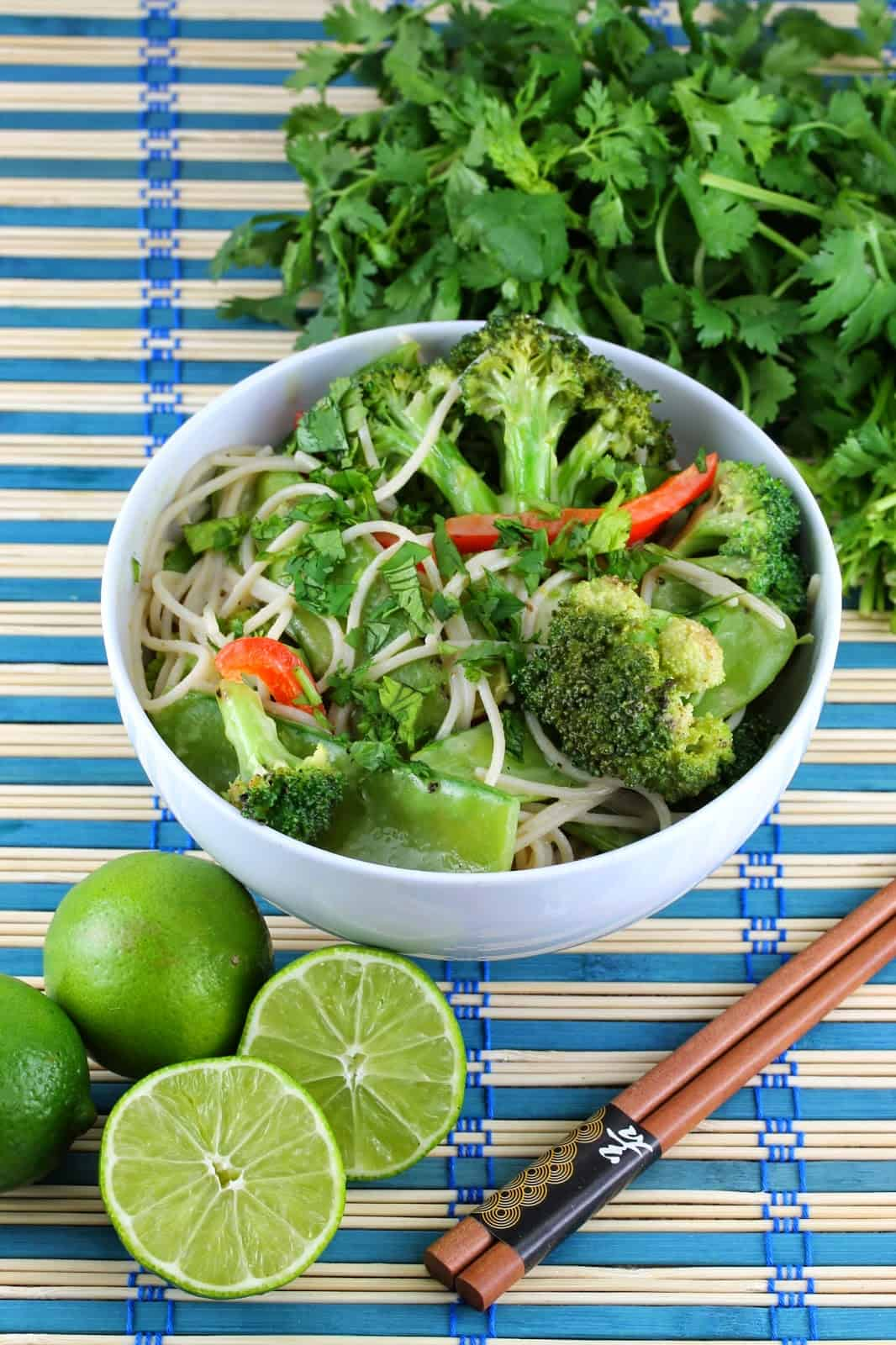 Thai green curry coconut stir fry in white bowl with chopsticks to the side