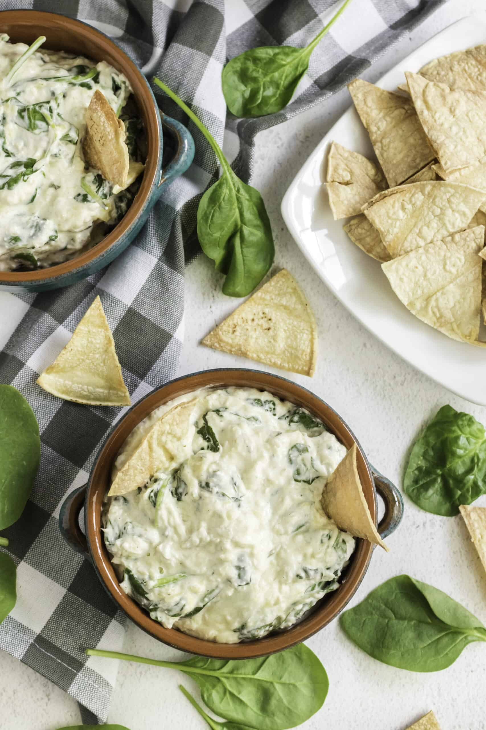 overhead shot of spinach artichoke dip in a bowl surrounded by tortilla chips and fresh spinach