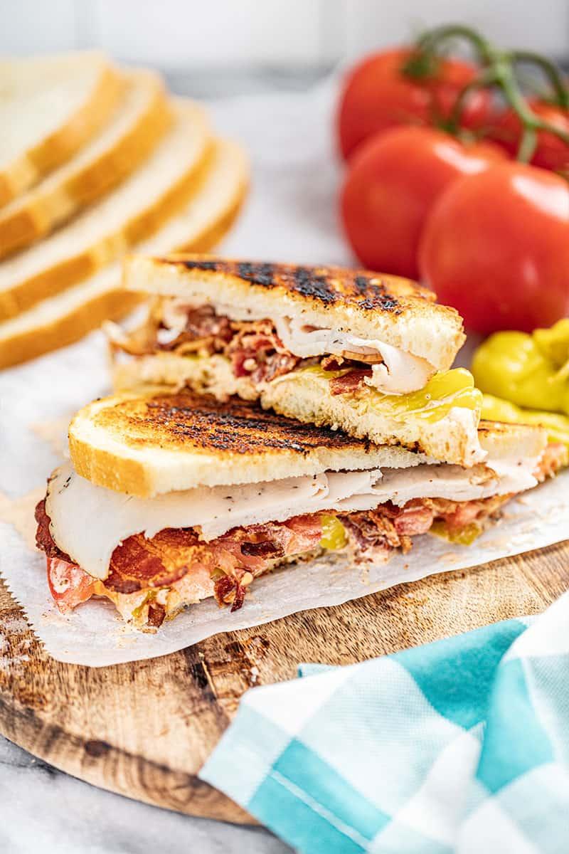 baja turkey club sandwich cut in half on a wooden board with fresh tomatoes in background