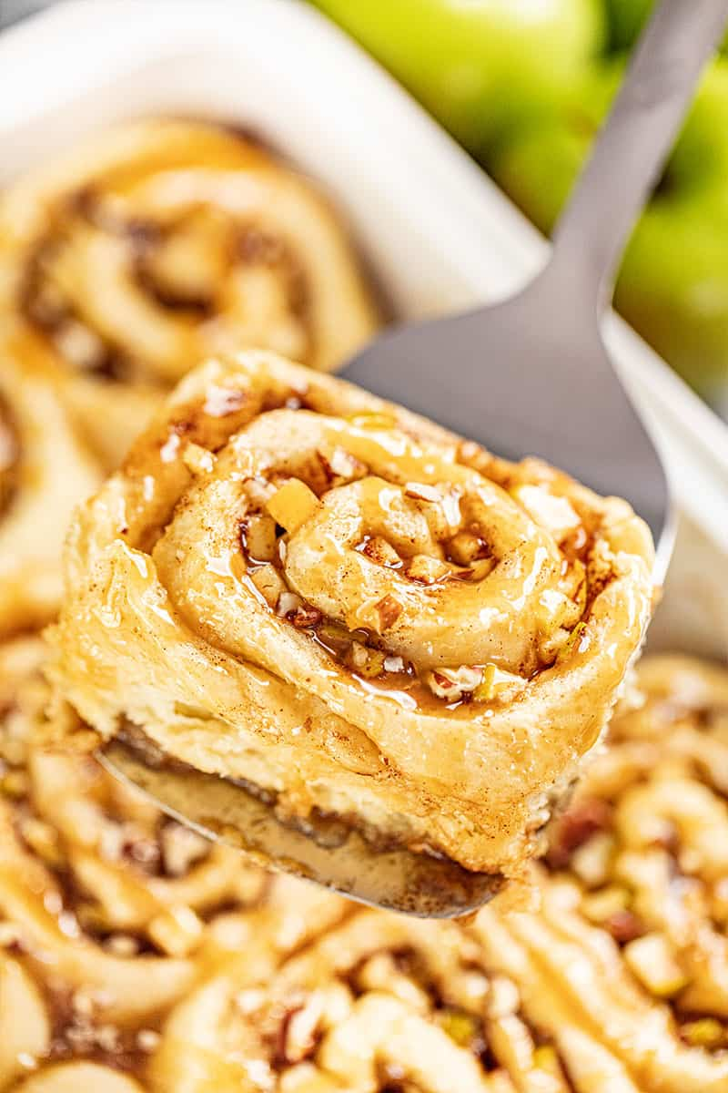 A close up view of a caramel apple cinnamon roll on a spatula