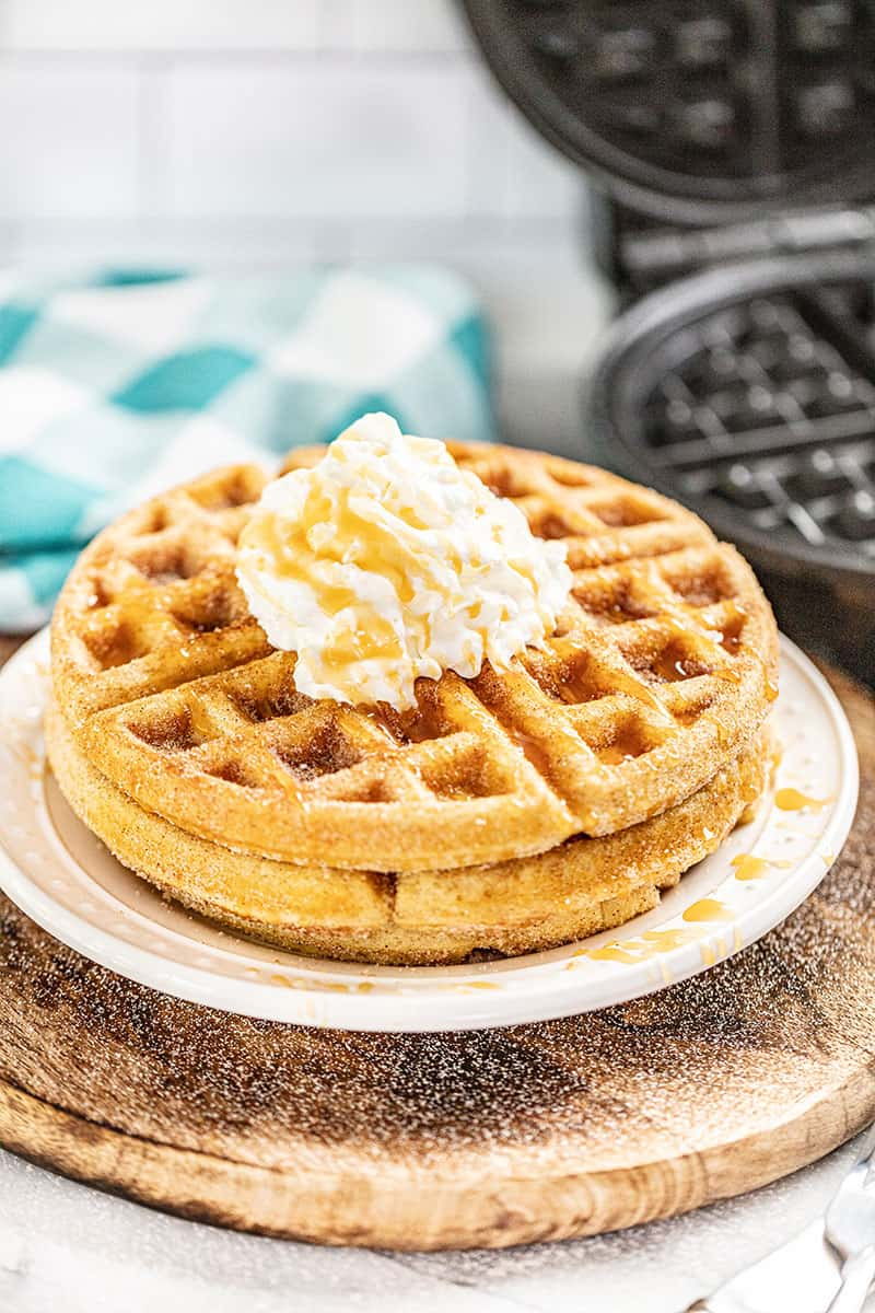 caramel churro waffles son a white plate with a spoonful of butter