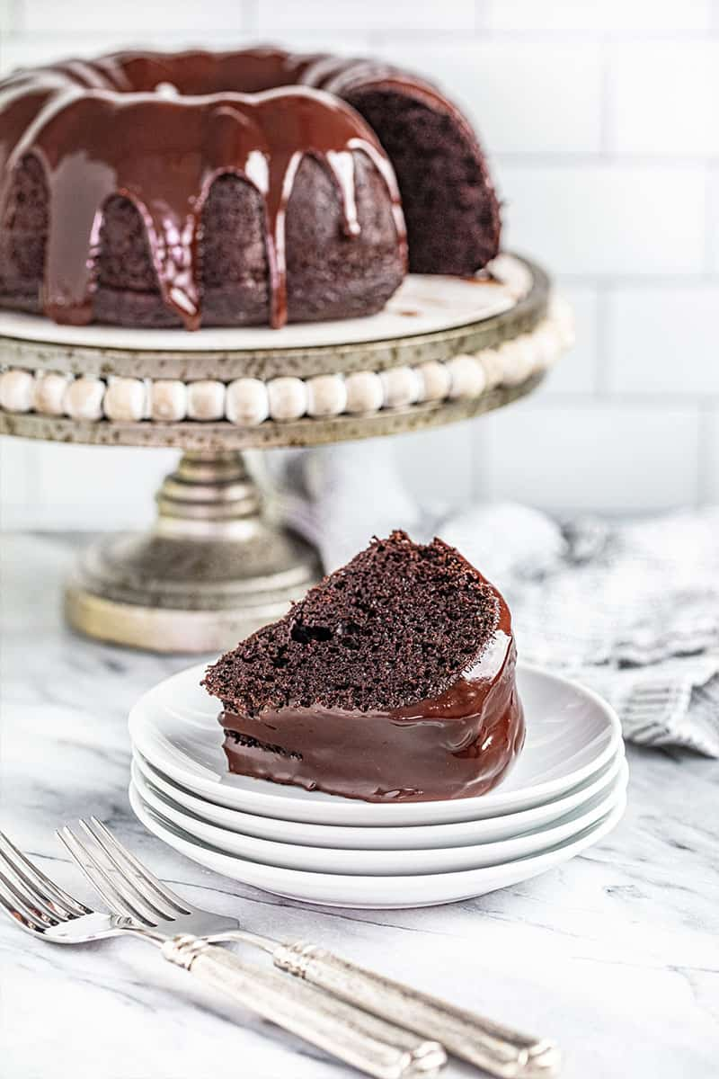 a slice of chocolate bundt cake served on a stack of small plates with the rest of the cake on a cake stand in the background