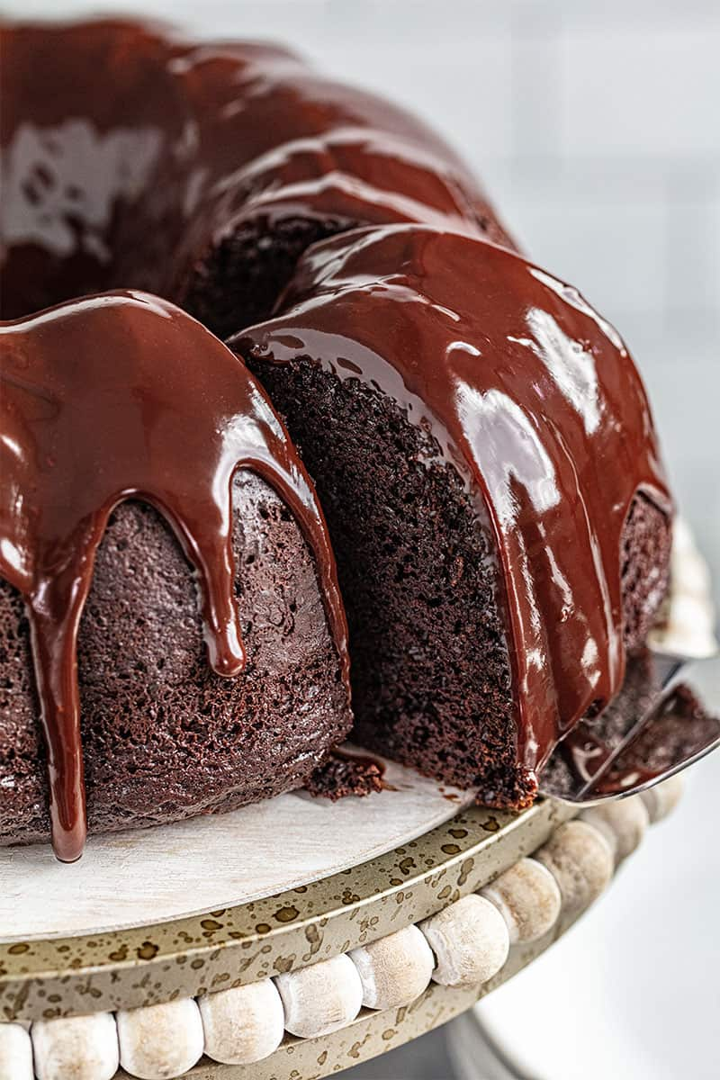 a cake server sliding a piece of chocolate bundt cake away from the rest of the cake.