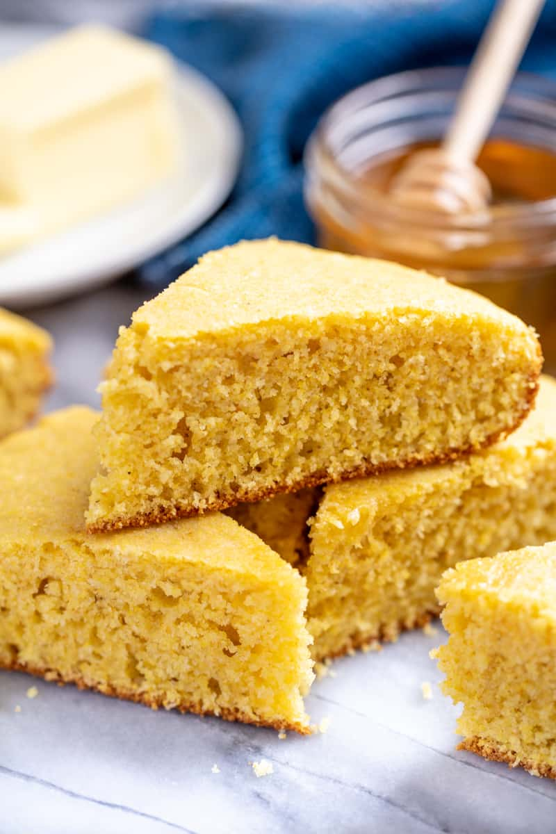 A pile of sliced cornbread with honey and butter in the background