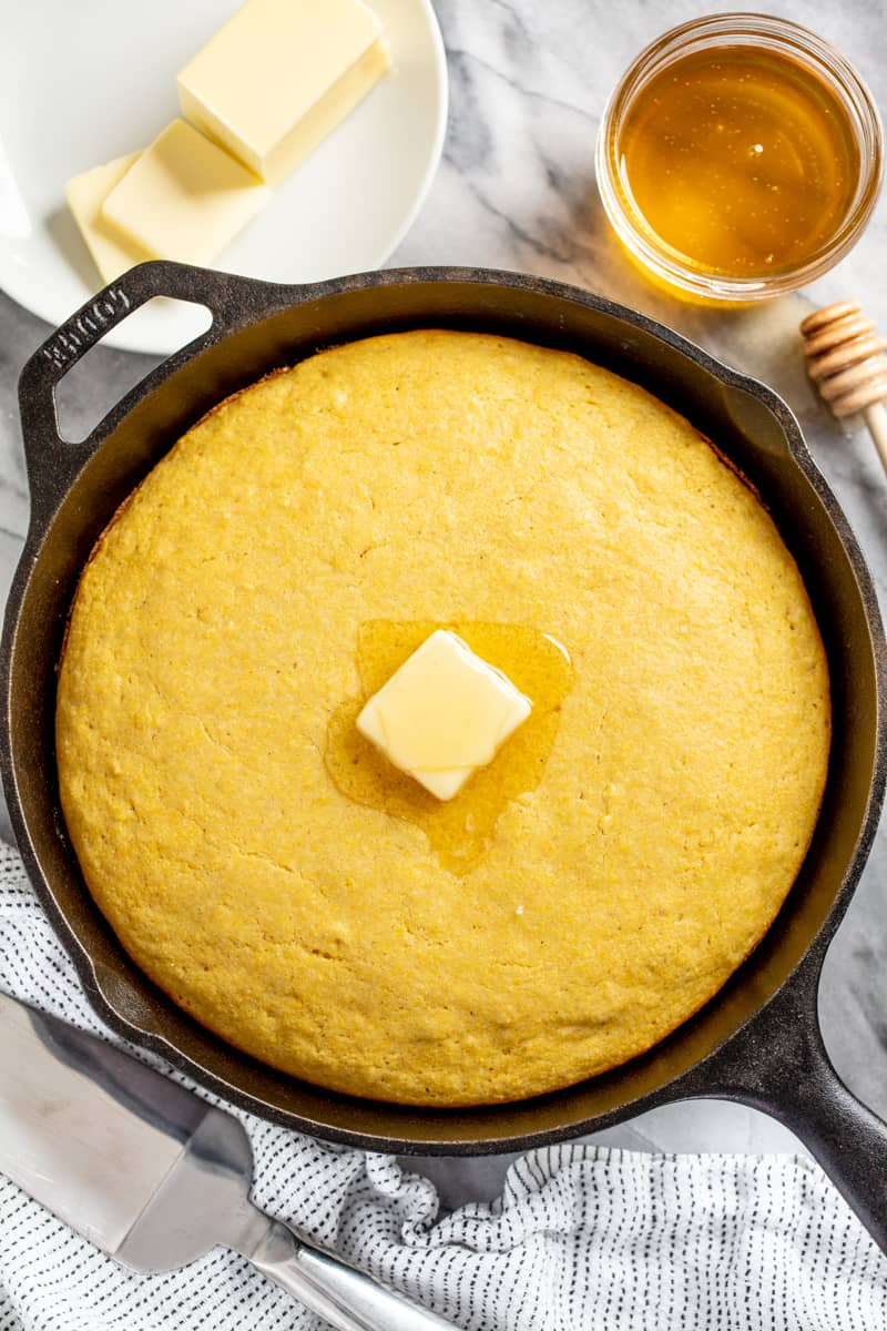 Cornbread in a skillet with a pat of butter on top