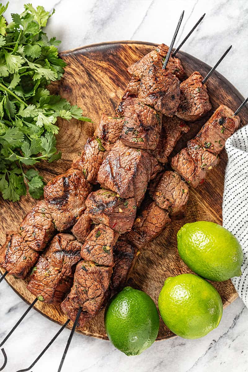 marinated beef kabobs on a wooden board with cilantro nearby