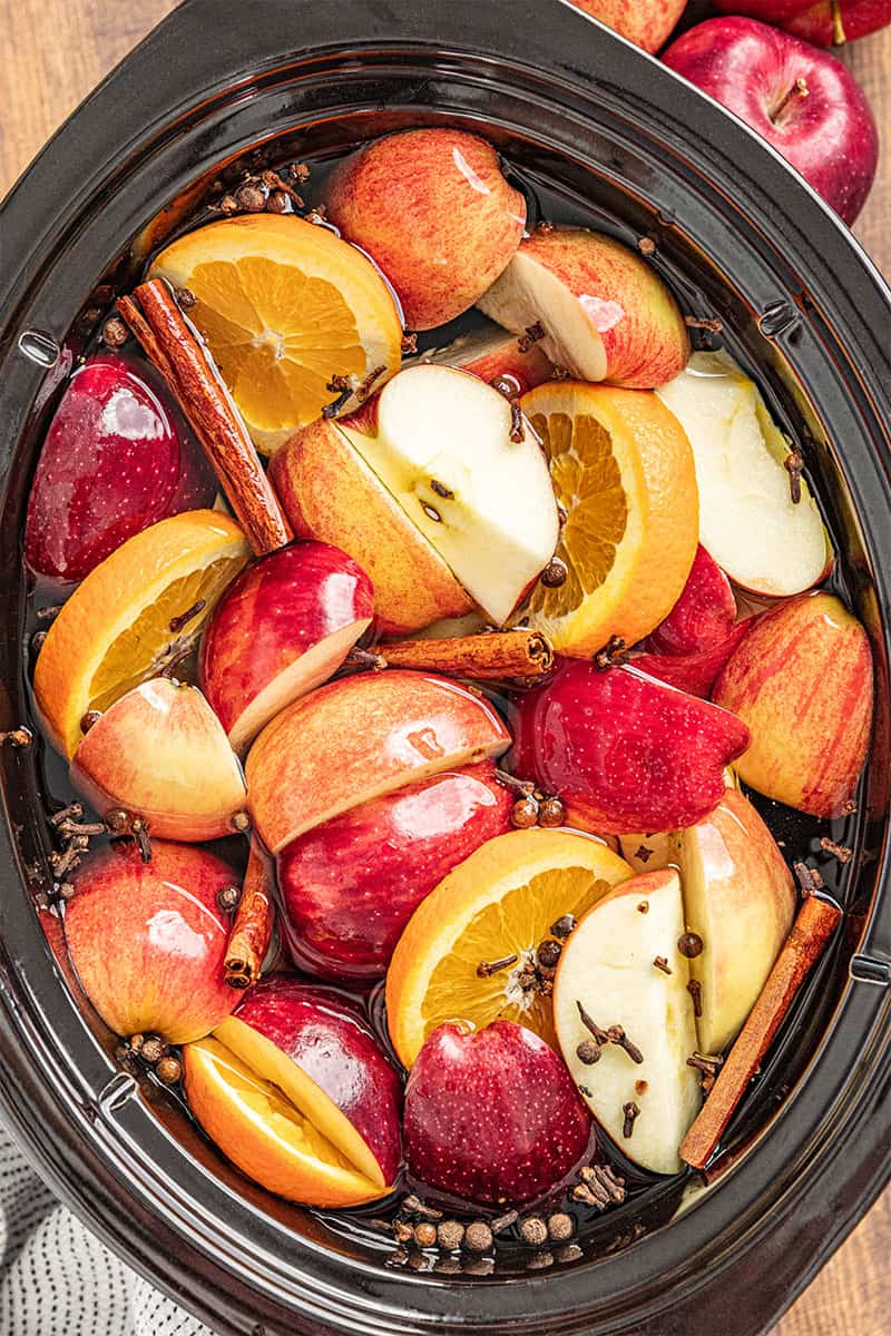 a crockpot full of apples, oranges, and spices for apple cider
