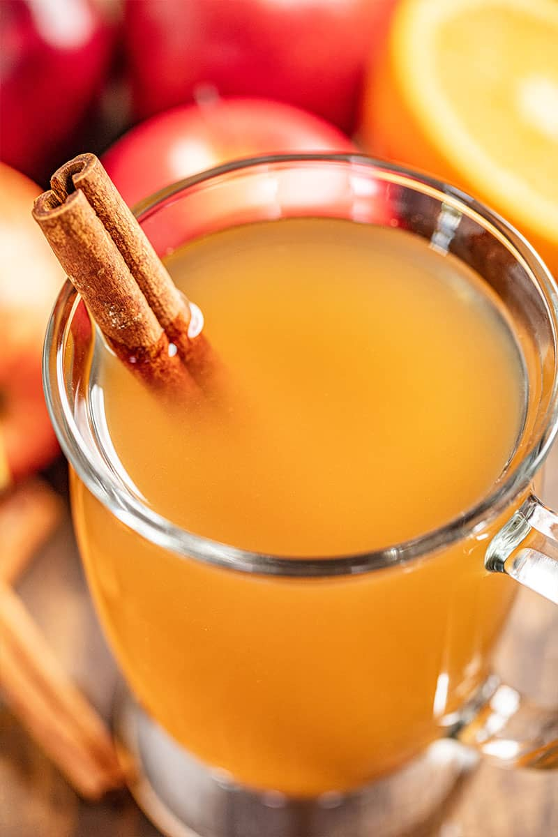 A glass mug full of apple cider with a cinnamon stick