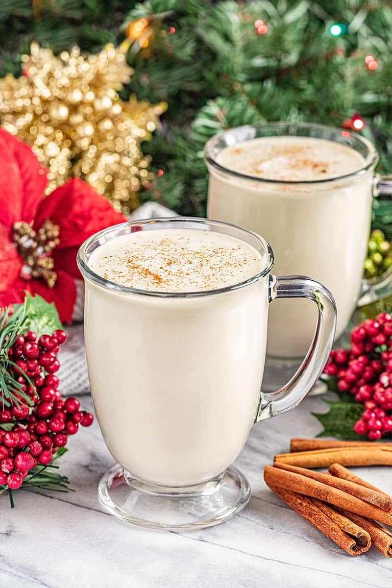 2 glass mugs of homemade eggnog with a Christmas tree and holly and ivy in the background.