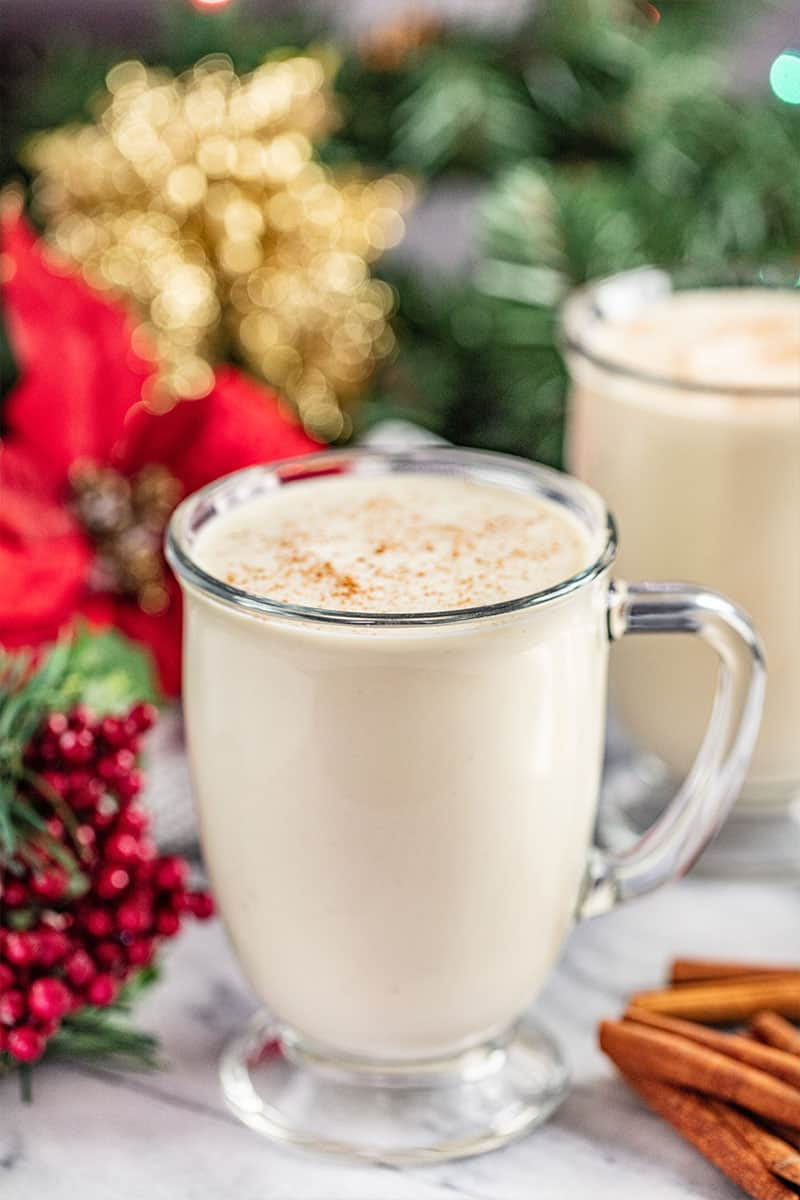 glass mugs filled with eggnog with cinnamon sticks next to the glasses