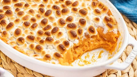 Sweet potato casserole in a baking dish with a spoonful removed.