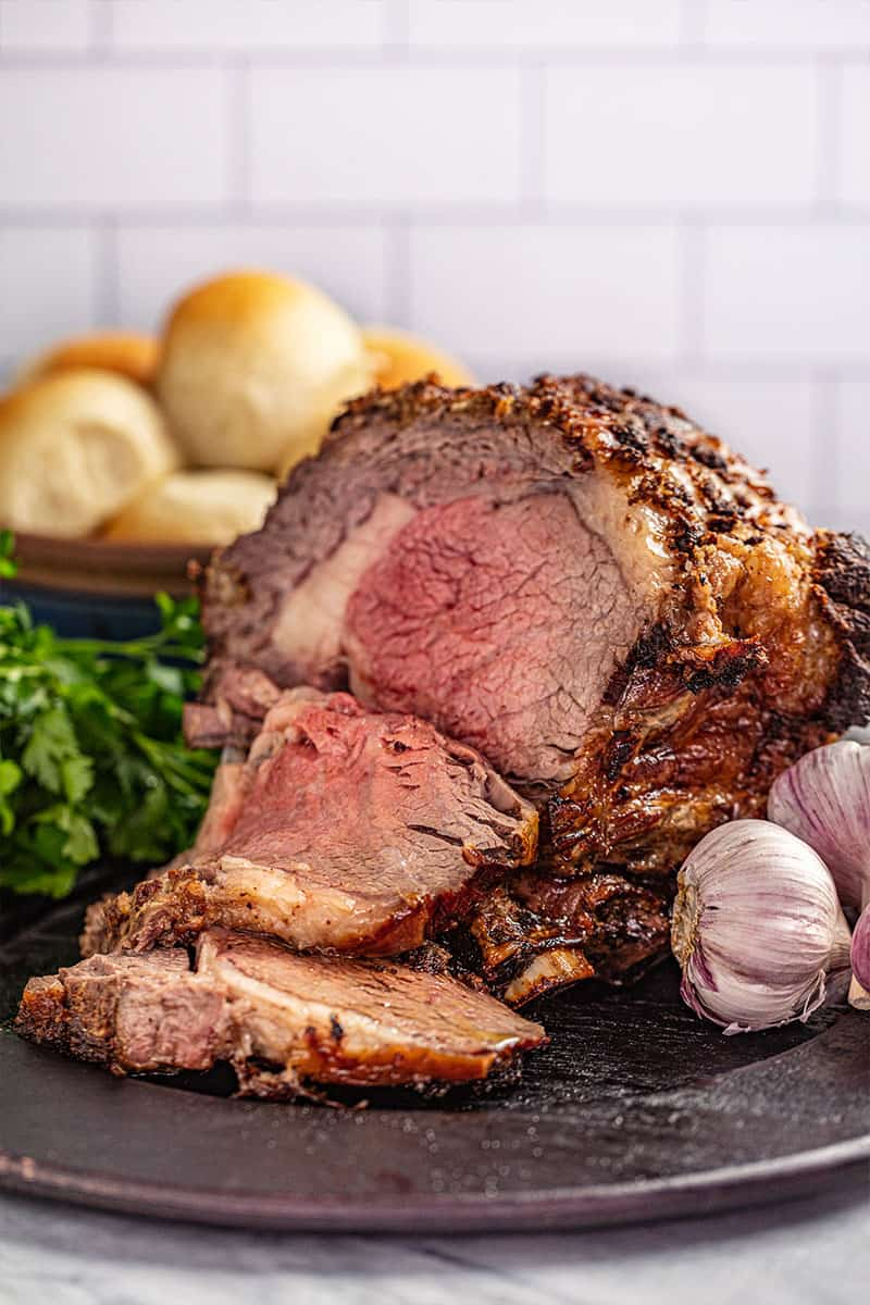 A prime rib roast crusted with horseradish and on a platter.