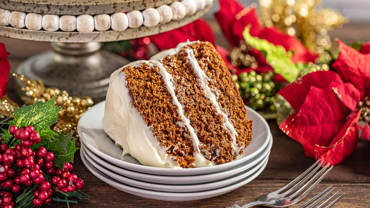 A slice of Christmas gingerbread cake on a stack of plates.
