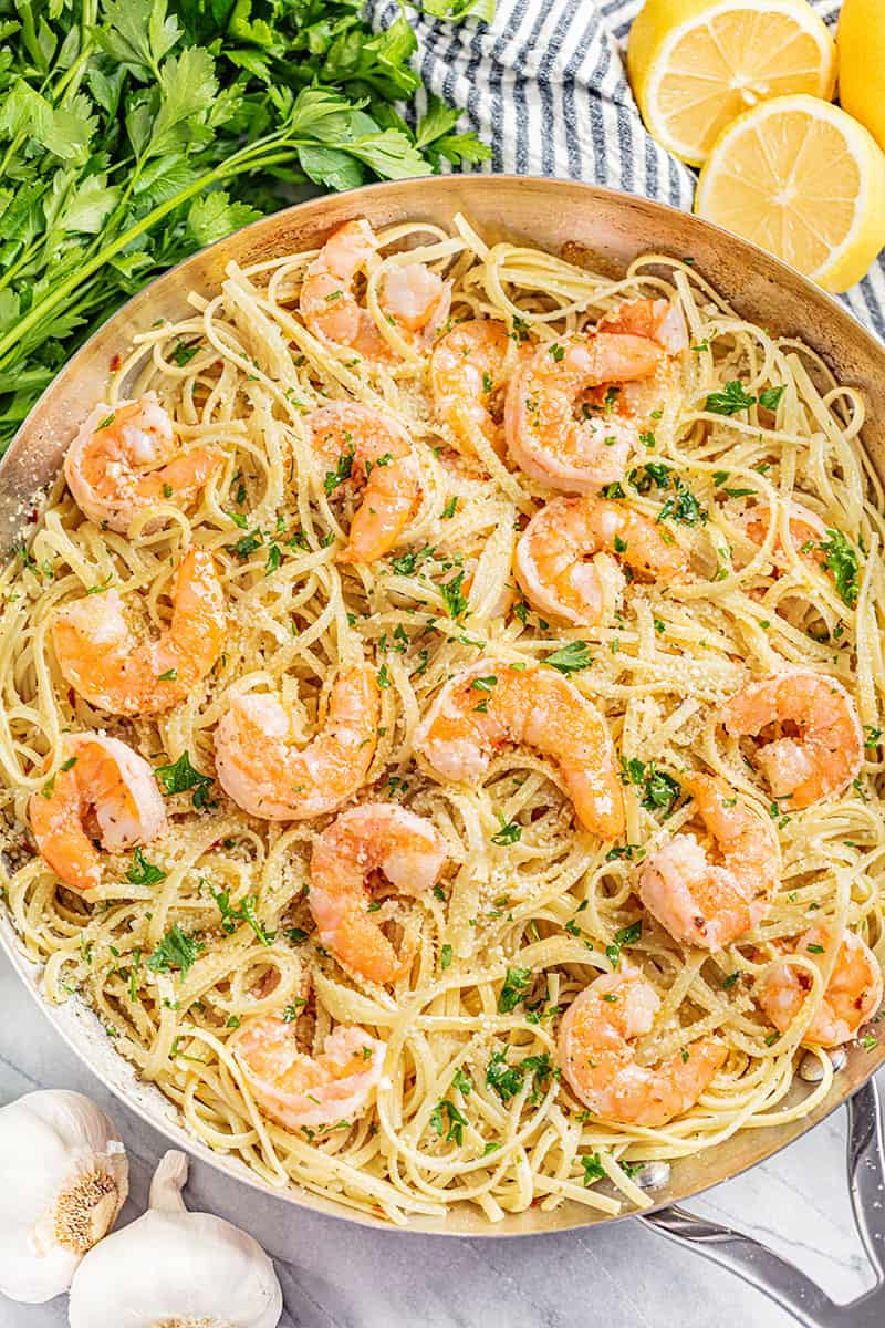 An overhead view of a skillet filled with shrimp scampi.