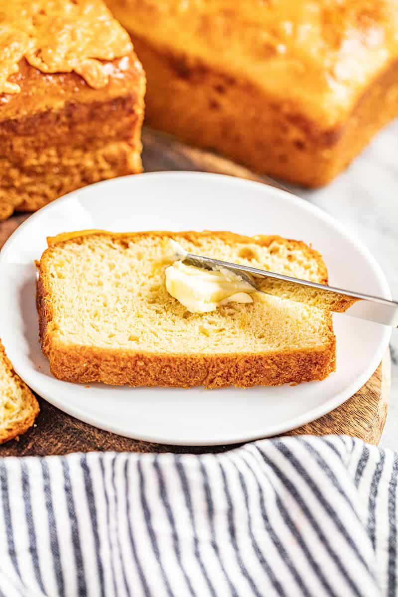 Butter being spread over a slice of cheddar batter bread.