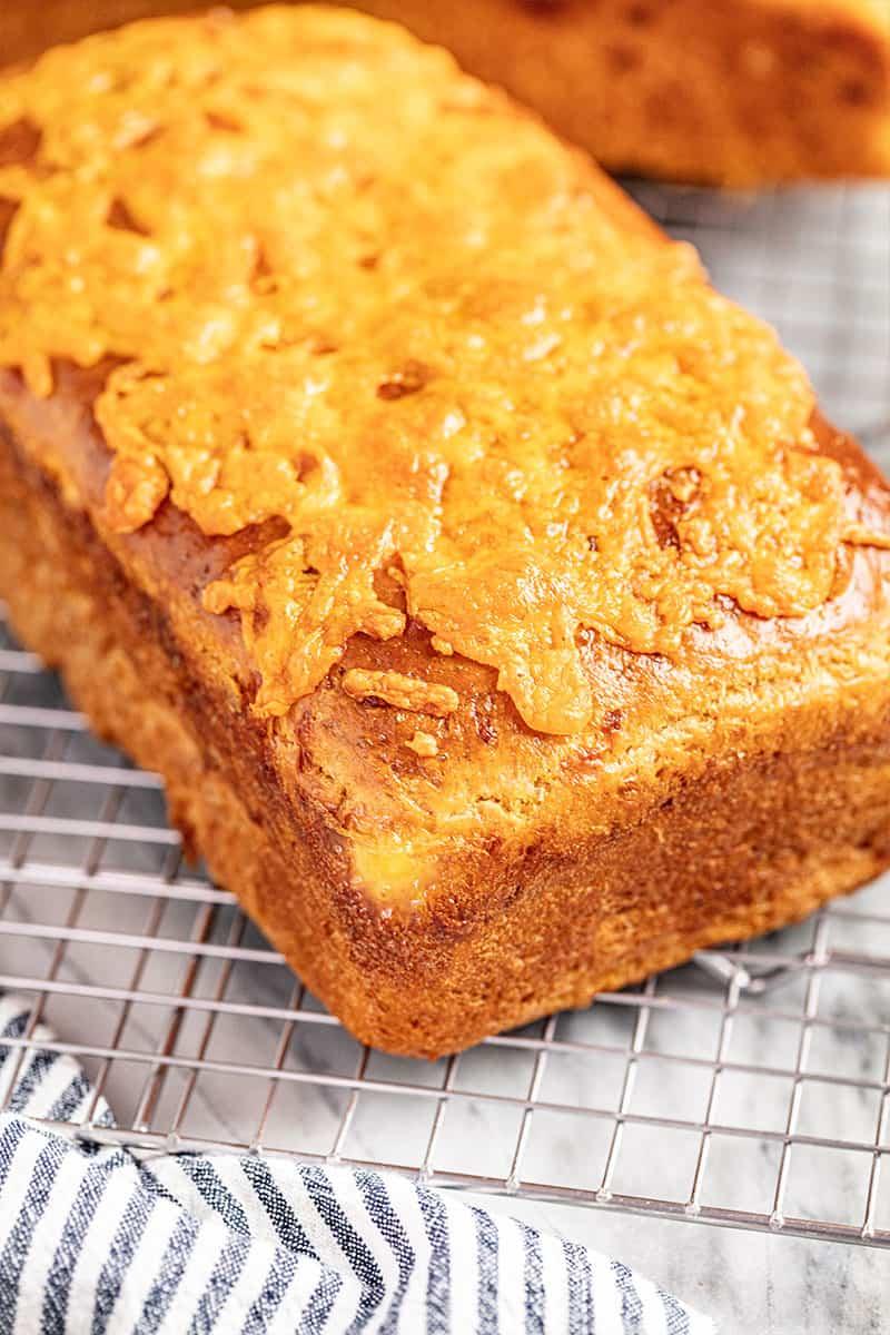 A loaf of cheddar batter bread on a cooling rack.