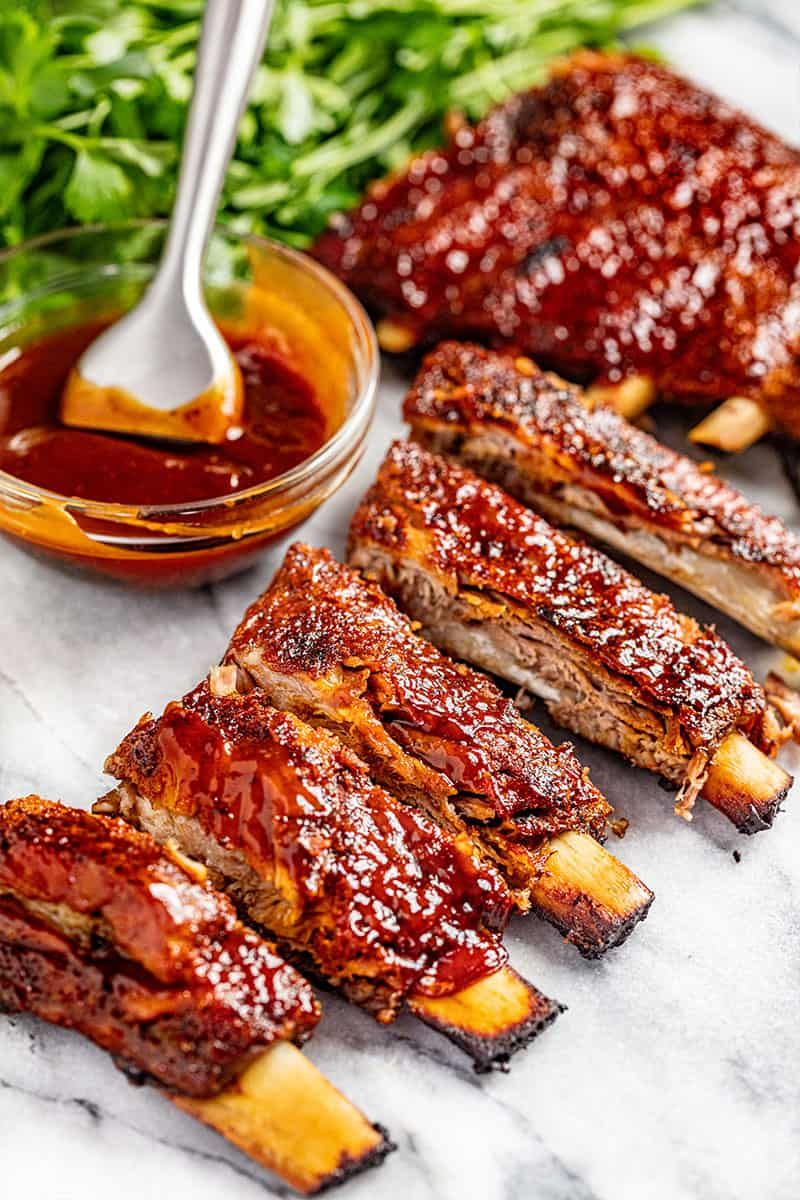 Oven baked ribs with a bowl of sauce on the side.