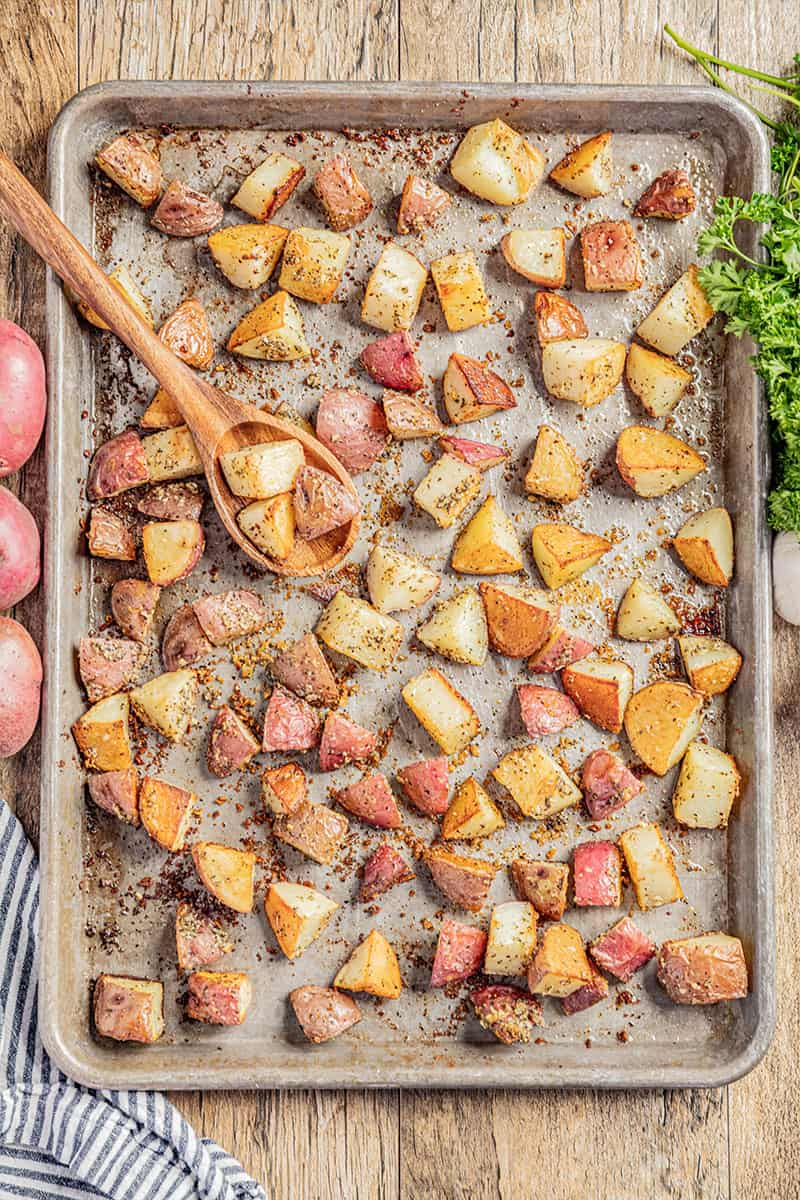 An overhead view of a sheet pan filled with roasted potatoes.