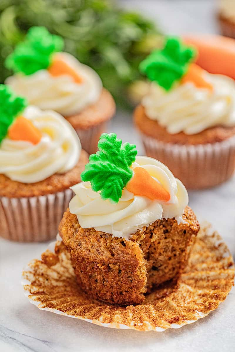 A carrot cake cupcake with cream cheese frosting with a bite taken out.