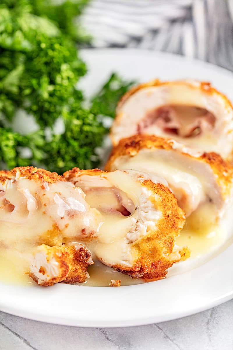 Chicken cordon bleu cut into pieces on a plate.