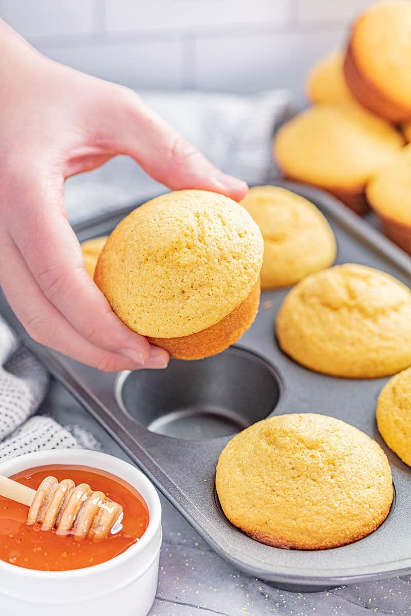 A person holding a cornbread muffin.