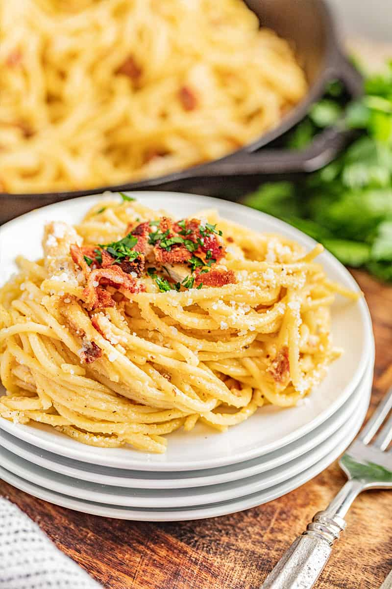 Chicken carbonara on a stack of plates.