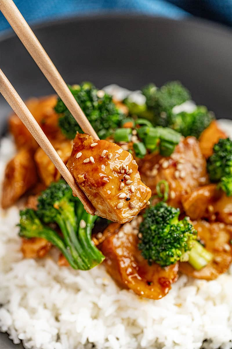 Chopsticks holding a piece of chicken teriyaki covered in sesame seeds.