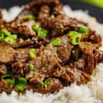 Korean Beef Bulgogi with chopped green onions on a bed of white rice.