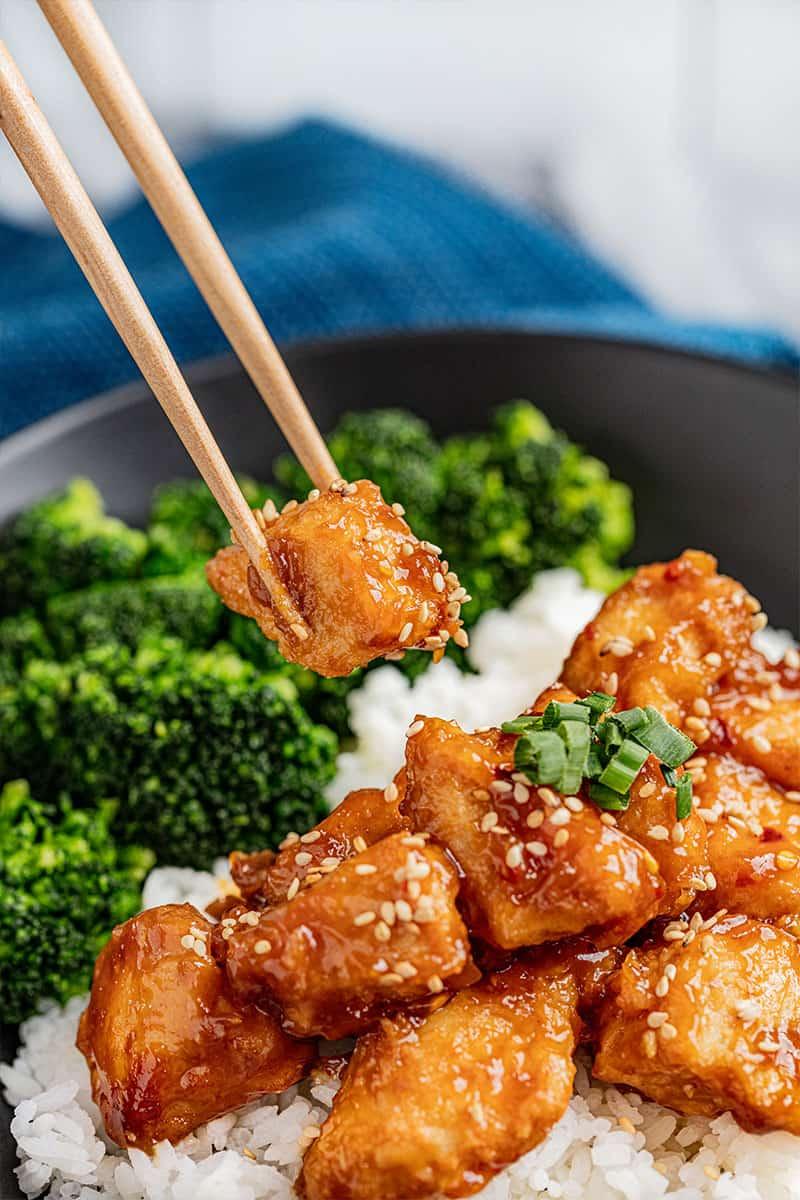 Chopsticks holding a piece of General Tso chicken.