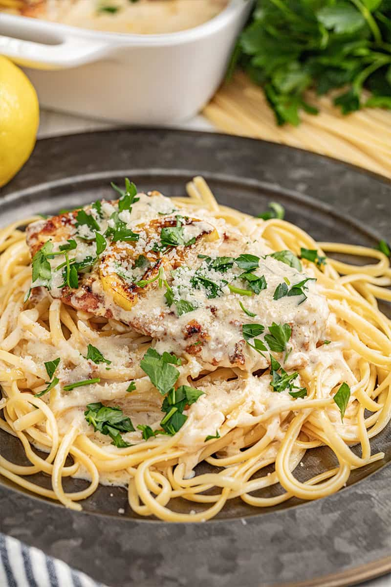 Chicken francese with spaghetti on a dinner plate.