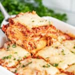 A spatula holding up a piece of ravioli lasagna.