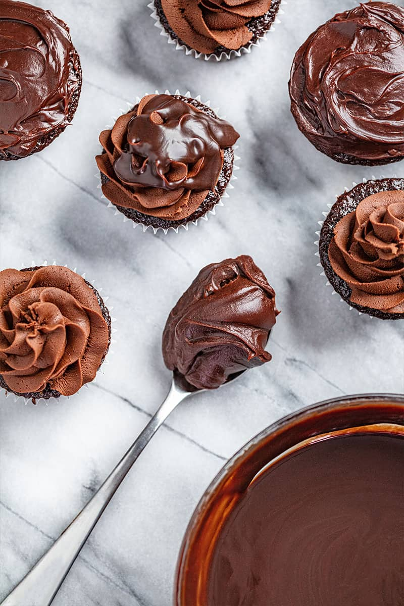 An overhead view of chocolate cupcakes with chocolate ganache.