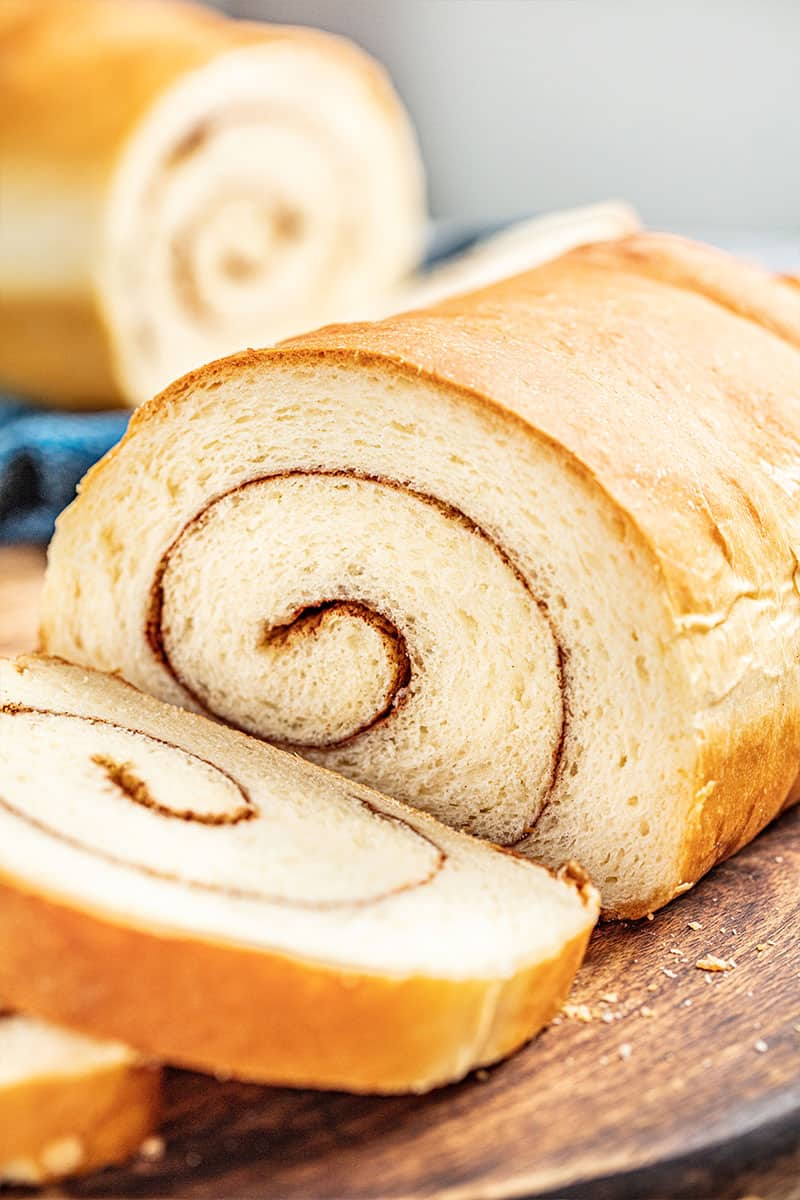 A loaf of cinnamon swirl bread with a slice cut off.