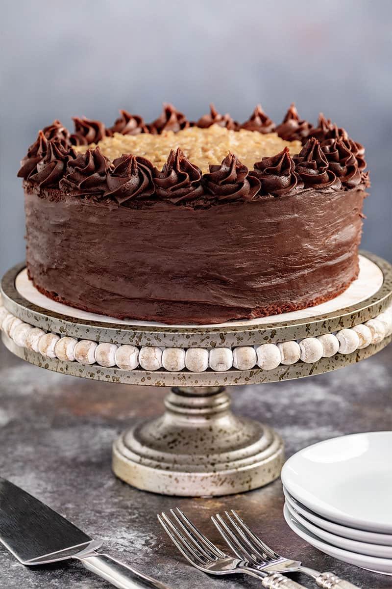 A whole German Chocolate Cake on a cake stand.