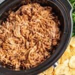 Overhead view of honey chipotle pulled pork in a slow cooker.