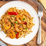 Overhead view of a white dinner plate with spicy cajun shrimp pasta.