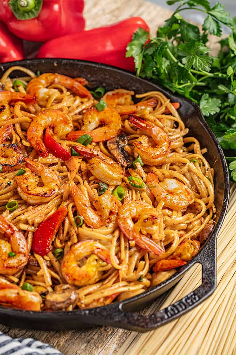 A cast iron skillet filled with creamy cajun shrimp pasta.
