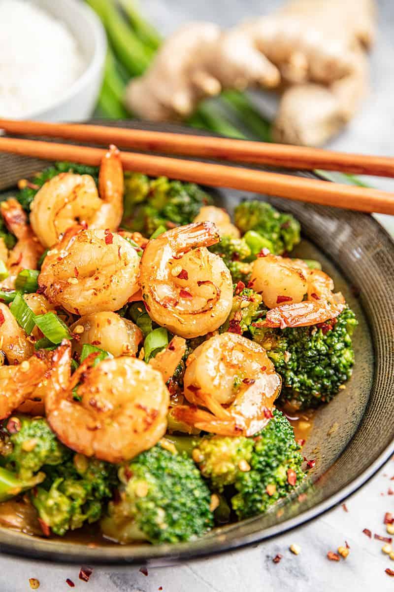 Spicy szechuan shrimp and broccoli with chopsticks.