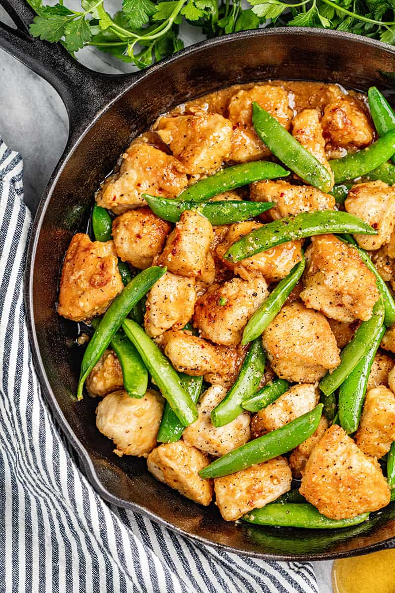 Overhead view of sticky honey garlic chicken and snap peas.