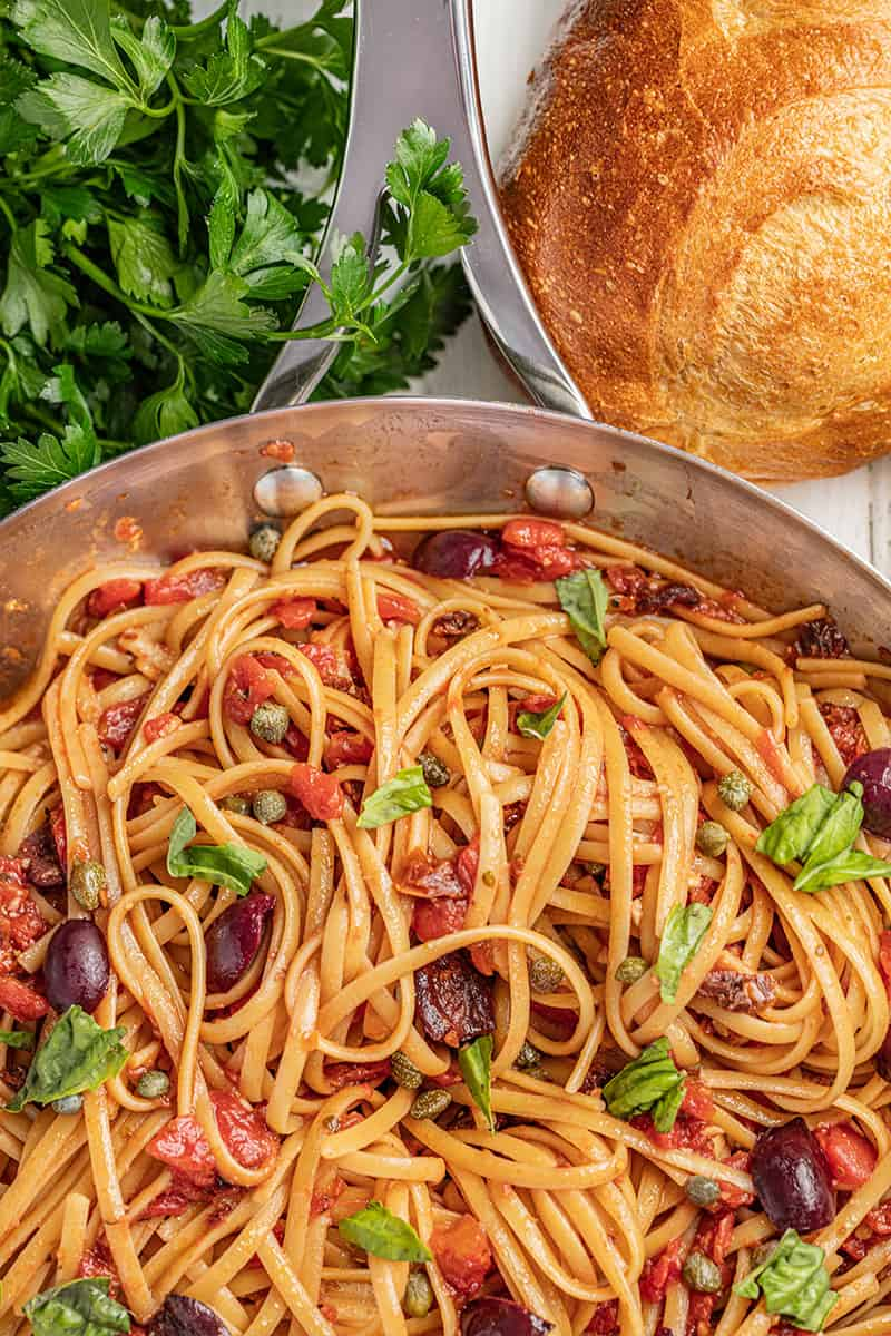 Pasta puttanesca with olives and basil.