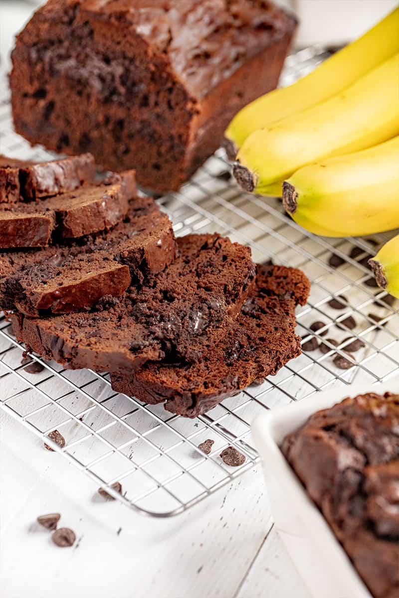 A loaf of chocolate banana bread cut into slices on a wire rack.