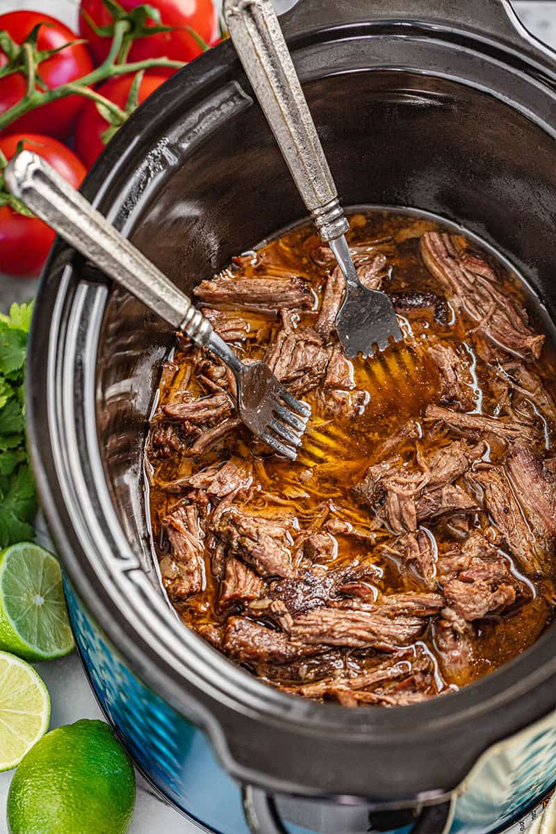 Overhead view looking inside a slow cooker with shredded beef and 2 forks inside.